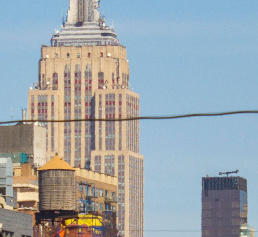 Crop 100%, prédios que estão longe parecem pintados em aquarela.