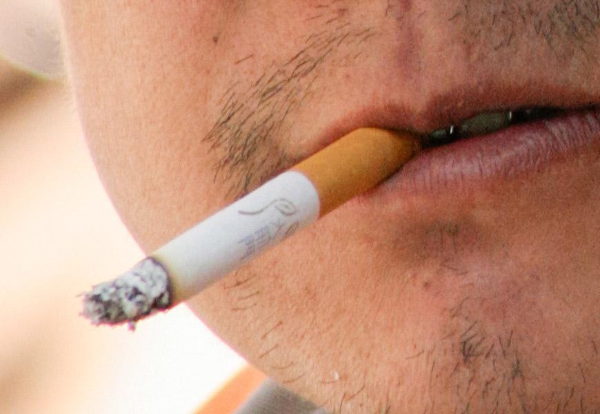 Crop 100%, detalhe a partir de um arquivo JPEG, textura da pele e inscrição no cigarro.