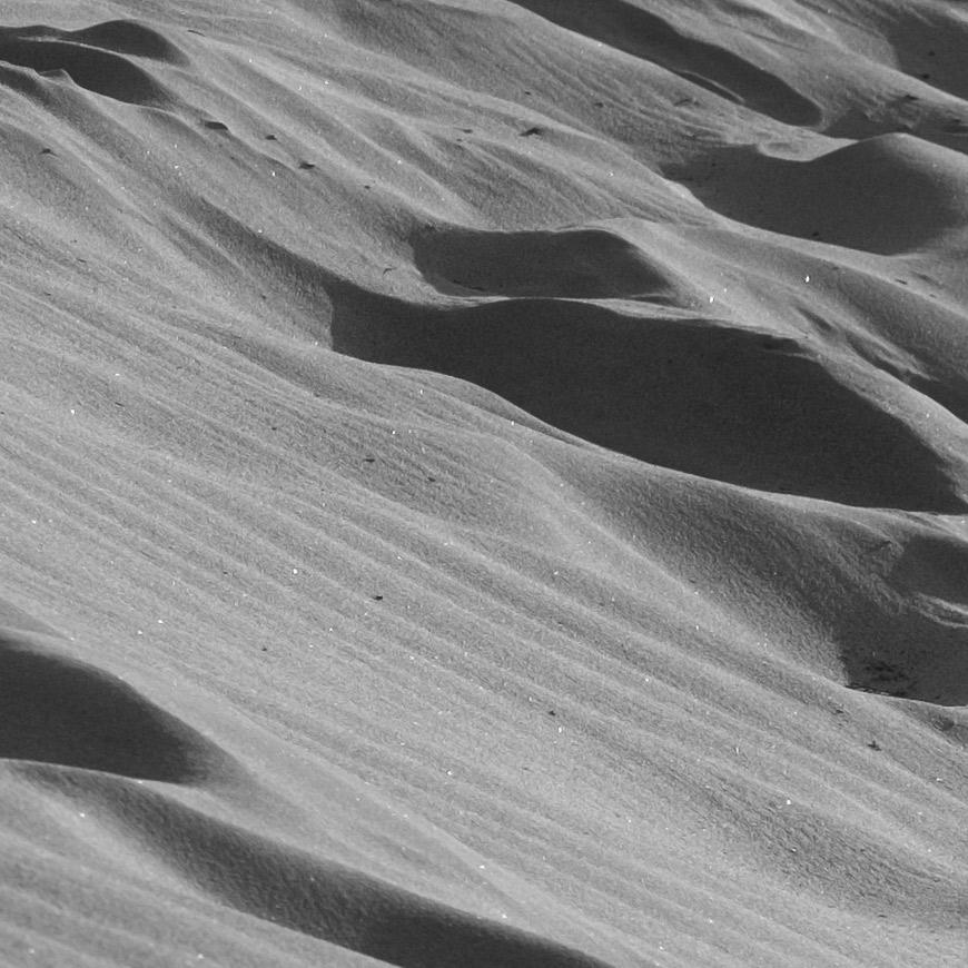 Crop 100%, grãos de areia reproduzidos no plano focal nítido.